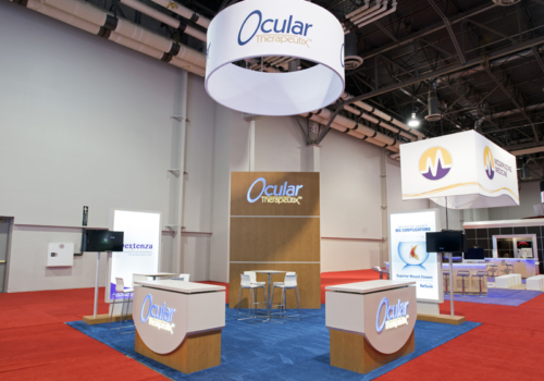 Ocular Therapeutix custom exhibit with round fabric hanging sign, counters and two monitors stands out on the show floor.