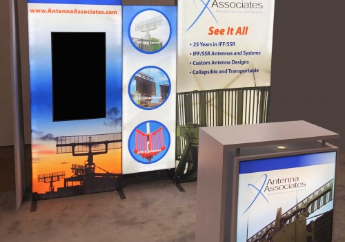 Custom modular LED backlit trade show display with vertically mounted monitor and branded backlit cabinet delivers vibrant graphics in a 10x10 booth space.