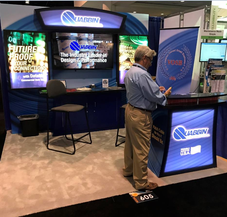 "This 10' x 10' custom booth features a backwall with vibrant backlit graphic panels, corporate branding and built-in storage with counter for displaying products. A wall-mounted 55"" smart monitor displays educational videos and a lighted reception counter, branded on all sides, and a seating area make engaging in conversations with show attendees easy and natural."