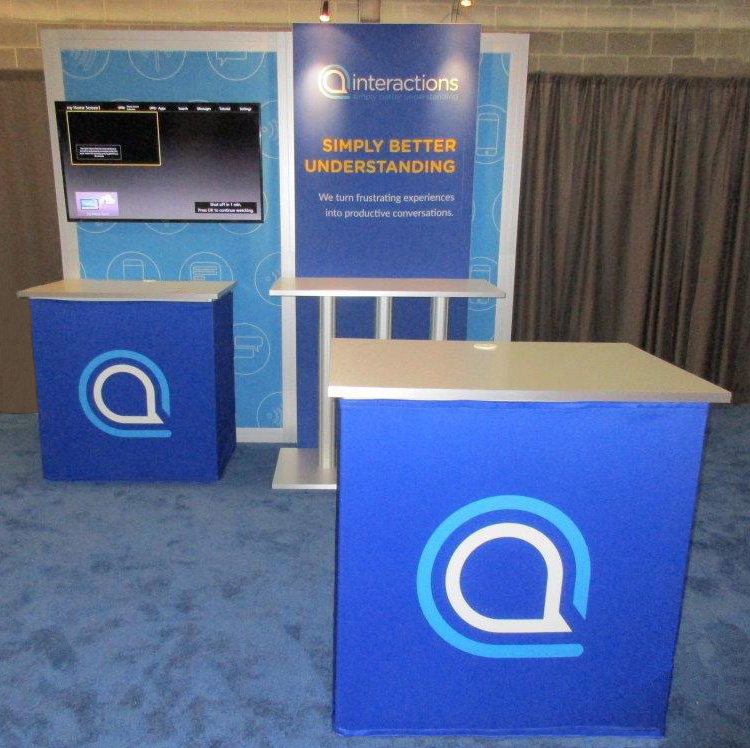 Interactions 10' portable exhibit with fabric graphics, large mounted flat-screen monitor, lighting, shelf and counters
