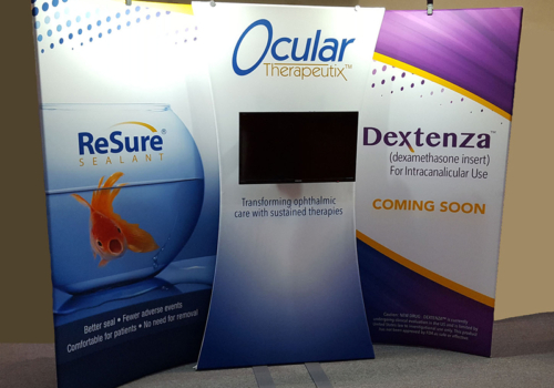 Ocular Therapeutix 10x10 curved portable fabric display with bold graphics, lighting and center fabric monitor stand