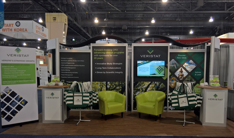 Veristat custom modular aluminum extrusion booth with graphics, monitor, counters, seating area, and wood-look flooring